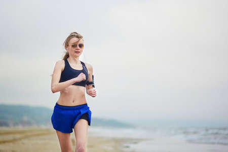 normandy: Young fitness running woman jogging fast on beach near ocean or sea on a foggy misty morning. Fitness and healthy lifestyle concept Stock Photo