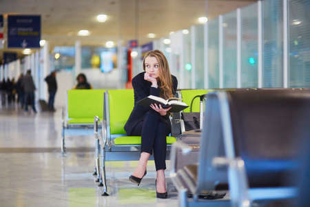 Young elegant business woman with hand luggage in international airport terminal, reading book while waiting for flight