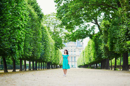 Beautiful young woman walking in Parisian Tuileries park on a summer day
