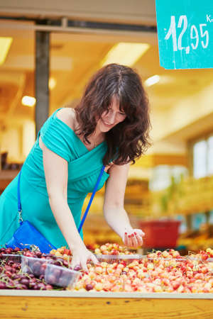Beautiful French woman choosing ripe organic cherries on a Parisian local market. Customer in food store, supermarket or hypermarket concept Stock Photo