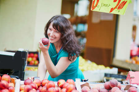Beautiful French woman choosing ripe organic peaches on a Parisian local market. Customer in food store, supermarket or hypermarket concept