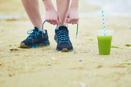 Young jogger with green vegetable smoothie, tying sport running shoes laces. Fitness and healthy lifestyle concept