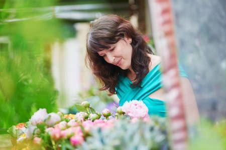 Beautiful French woman choosing flowers on a Parisian local market