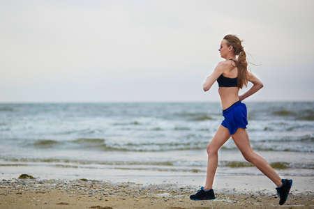 Jeune femme de remise en forme de course de jogging rapide sur la plage près de l'océan ou de la mer un matin brumeux brumeux. Fitness et le concept de mode de vie sain Banque d'images - 74866591