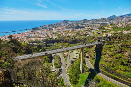 Aerial scenic view of Funchal and large motorway with Atlantic ocean, Madeira island, Portugal
