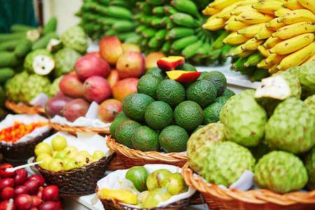 Fresh and ripe exotic fruits on traditional farmer market Mercado dos Lavradores, Funchal, Madeira island, Portugal. Focus on avocado
