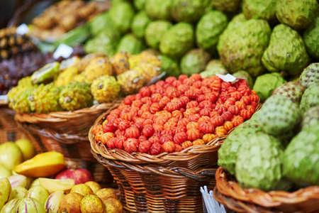 anona: Fresh and ripe exotic fruits on traditional farmer market Mercado dos Lavradores, Funchal, Madeira island, Portugal. Focus on pitanga fruits
