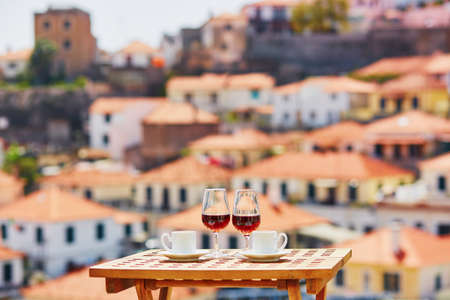 Two glasses of Madeira wine and two cups of fresh espresso coffee in cafe with view to Funchal town, Madeira, Portugal