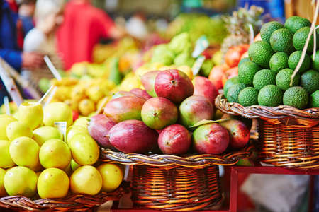 Fresh and ripe exotic fruits on traditional farmer market Mercado dos Lavradores, Funchal, Madeira island, Portugal. Focus on mango