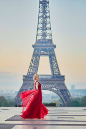 Beautiful young woman in long red dress dancing near the Eiffel tower in Paris, France