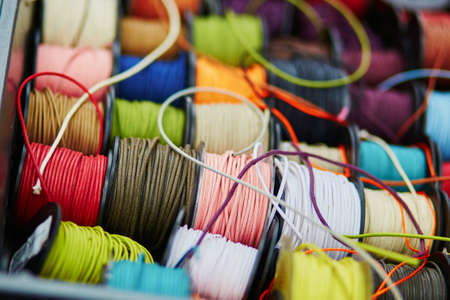 stitchwork: Variety of spools with rope of different colors for sewing or crafting on a market