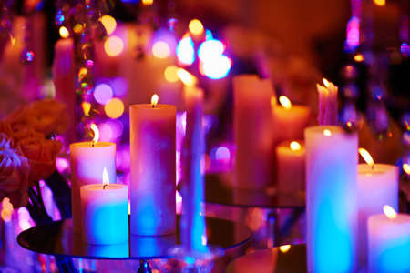 Beautiful table set with candles for a festive event, party or wedding reception, in purple light Stock Photo