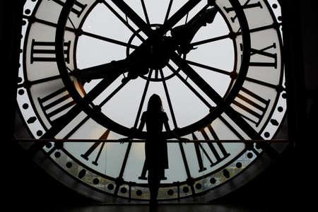 numeros romanos: Woman silhouette standing in front of large clock, Paris, France. Unrecognizable person overlooking Paris Foto de archivo