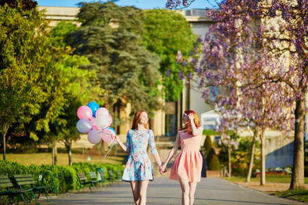 Two beautiful young women with bunch of balloons in Paris on a spring day Фото со стока