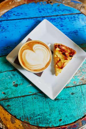 カプチーノ コーヒーとアップルパイ色鮮やかな緑と青のカフェ テーブルの上の大きなカップ
