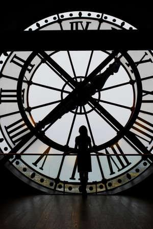 numeros romanos: Mujer silueta de pie delante del reloj grande, París, Francia. Persona irreconocible con vistas a París Foto de archivo