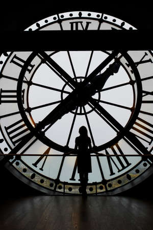 Woman silhouette standing in front of large clock, Paris, France. Unrecognizable person overlooking Paris Stock Photo