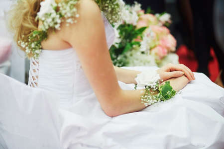 Young bride with beautiful flower decorations on her dress and wrist