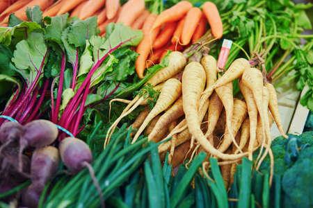 Large heap of fresh ripe organic parsnip and beet on farmer market in Paris, France