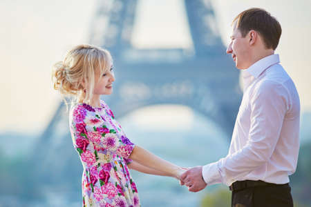Romantic loving couple holding each other hands near the Eiffel tower in Paris, France