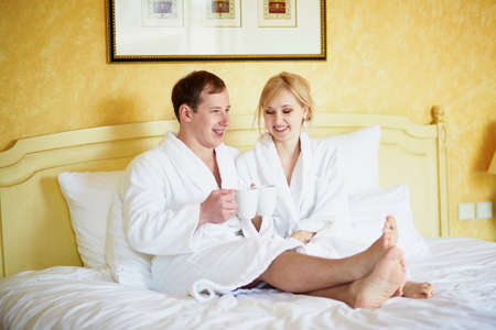 Happy young couple in white bathrobes drinking coffee together in bed at morning. Hotel, travel, relationships, and happiness concept
