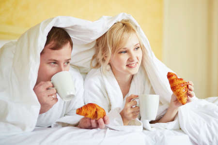 Happy young couple in white bathrobes drinking coffee and eating croissants together in bed at morning. Hotel, travel, relationships, breakfast in bed and happiness concept Stock Photo