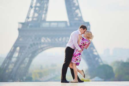 Romantic loving couple kissing near the Eiffel tower in Paris, France Stock Photo