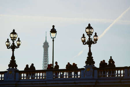 Scenic cityscape of Paris with silhouettes of people and lanterns on the famous Alexandre III bridge and the Eiffel tower over the blue sky