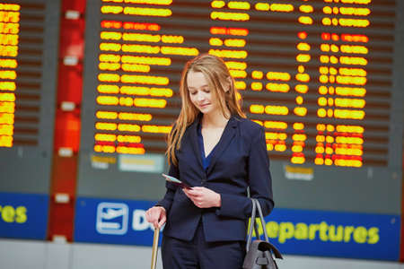 Young elegant business woman with hand luggage in international airport terminal, looking at information board, checking her flight. Cabin crew member with suitcase. Imagens
