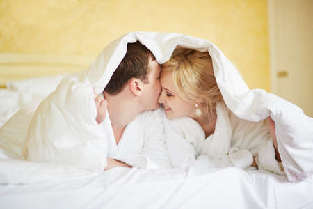 Happy young couple in white bathrobes together in bed at morning. Hotel, travel, relationships, and happiness concept