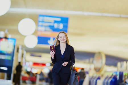 Young elegant business woman with hand luggage walking through the international airport terminal. Girl holding French passport and boarding pass. Cabin crew member with suitcase Imagens