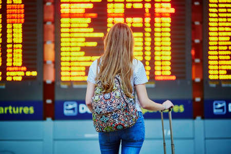 Beautiful young tourist girl with backpack and carry on luggage in international airport, near flight information board Stock Photo