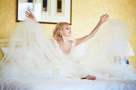 Cheerful young bride in wedding dress waiting for groom to come and enjoying the morning of her special day at home or in hotel room
