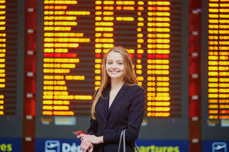 Young elegant business woman with hand luggage in international airport terminal, looking at information board, checking her flight. Cabin crew member with suitcase. Stock Photo
