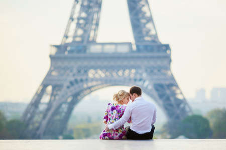 Romantic loving couple sitting on the ground near the Eiffel tower in Paris, France