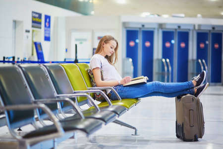 Young traveler with carry on luggage in international airport reading a book while waiting for her flight