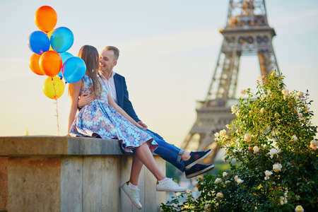 Romantic couple with colorful balloons near the Eiffel tower in Paris, France