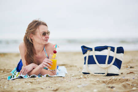 paper umbrella: Beautiful young woman relaxing and sunbathing on beach, drinking delicious fruit or alcohol cocktail with paper umbrella, beach bag on sand near the model