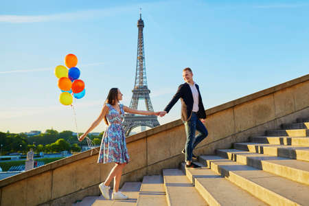 Romantisch paar met kleurrijke ballonnen in de buurt van de Eiffeltoren in Parijs, Frankrijk, lopen de trap op