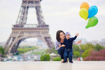 에펠 탑 근처 파리에서 다채로운 풍선의 무리와 함께 행복 한 가족. 프랑스에서 휴가를 즐기는 어머니와 어린 아들