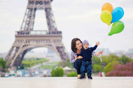 Happy family of two with bunch of colorful balloons in Paris near the Eiffel tower. Mother and little son enjoying their vacation in France Stock Photo