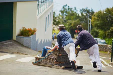 有名なソリ競技者は伝統的な移動杖、フンシャル、マデイラ島、ポルトガルの通り下り坂そり