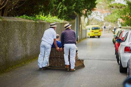 Célèbre cavaliers de luge en train de déplacer la luge de canne traditionnelle dans les rues de Funchal, île de Madère, Portugal Banque d'images - 80818741