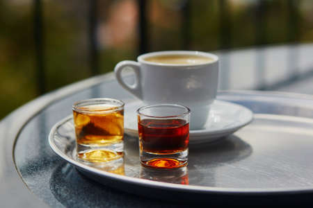 Two glasses of Madeira wine and cup of fresh espresso coffee in cafe at Funchal, Madeira, Portugal Banco de Imagens