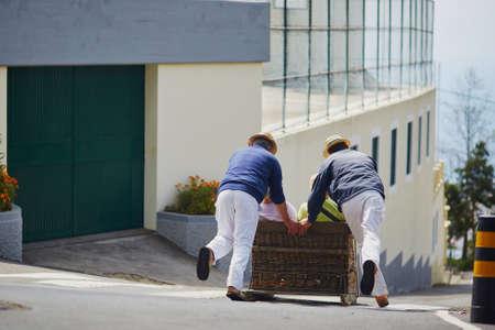Berühmte Tobogganfahrer, die traditionellen Cane-Schlitten bergab auf den Straßen von Funchal, Madeira-Insel, Portugal bewegen Standard-Bild - 80805823