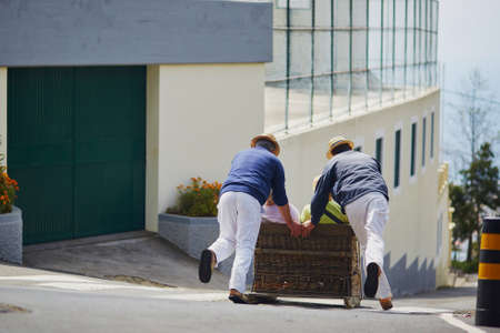 Famous toboggan riders moving traditional cane sledge downhill on the streets of Funchal, Madeira island, Portugal