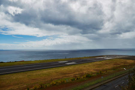 View of Madeira airport Cristiano Ronaldo runway near the ocean with dramatic sky