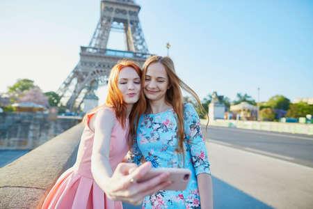 Twee vrienden nemen zelfie in de buurt van de Eiffeltoren in Parijs, Frankrijk