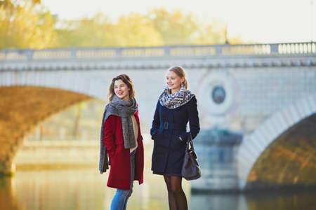 日当たりの良いをパリで一緒に歩いて 2 つの若い女の子は落ちる日です。観光や友情の概念