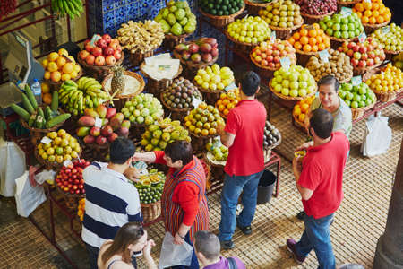 FUNCHAL, PORTUGAL - MARCH 20: People shopping at the famous Mercado dos Lavradores on March 20, 2017 at Funchal, capital city of Madeira, Portugal 스톡 콘텐츠